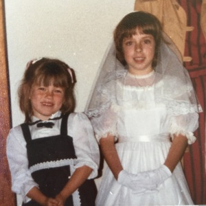 Rocking a bowl cut at my first communion. Erin, age 5, Danielle, age 7.